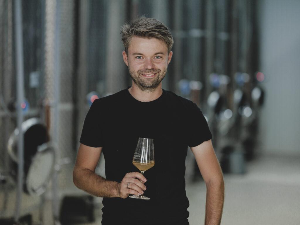 Alexander Waberer mit Weinglas im Weinkeller